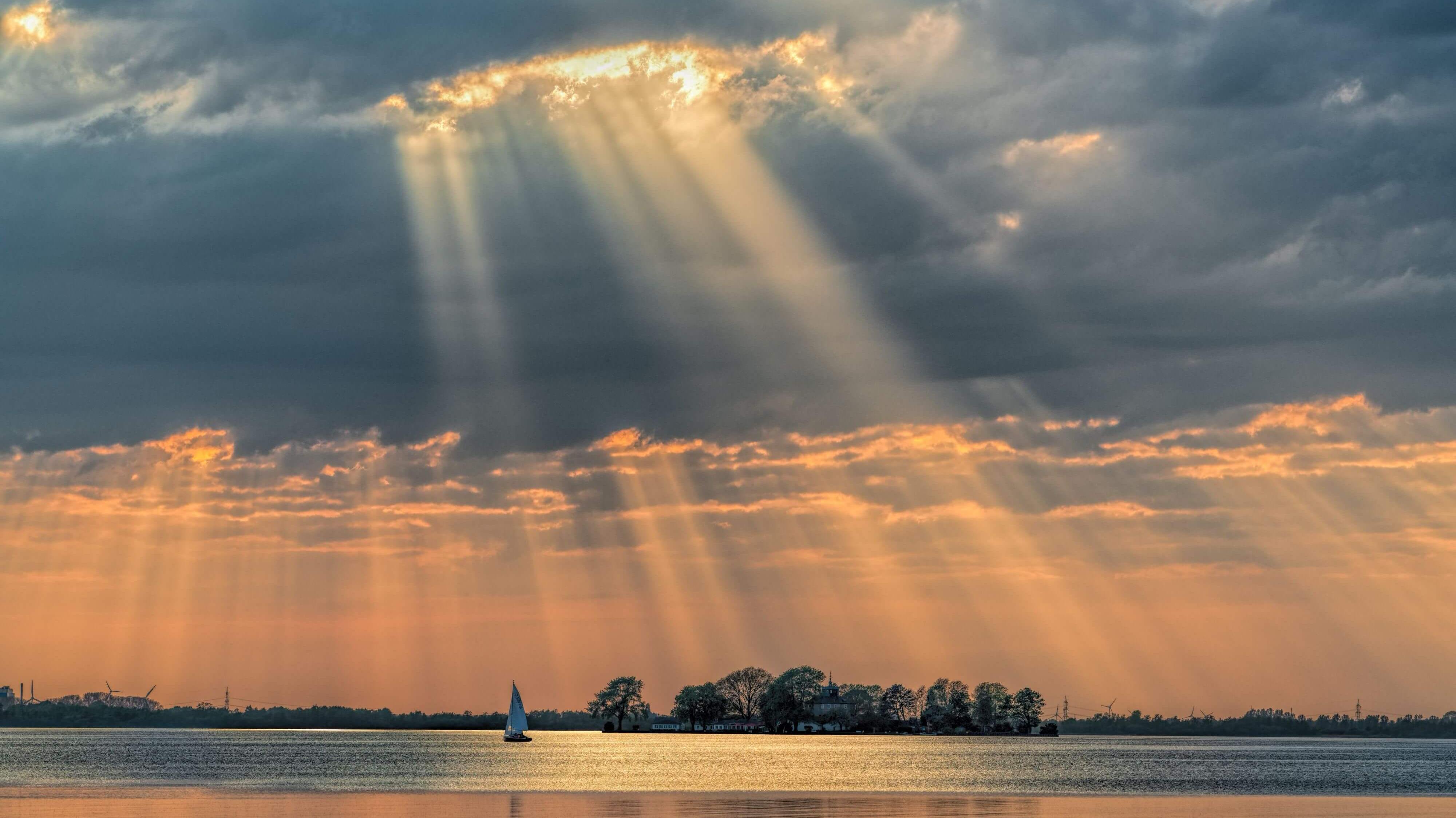 83bbd617593b40 Abendliche Sonnenstrahlen brechen durch die Wolkendecke und tauchen den  Wilhelmstein in ein orangefarbenes Licht.